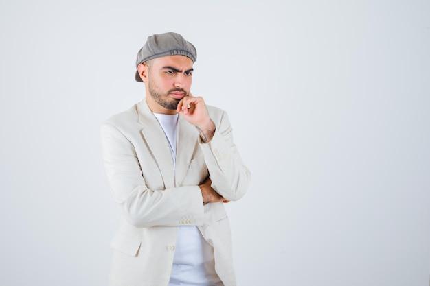 Jovem de camiseta branca, jaqueta e boné cinza em pose pensativa e pensativo