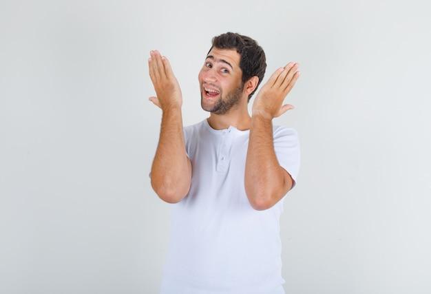 Jovem de camiseta branca levantando as palmas das mãos e apertando as mãos e parecendo alegre