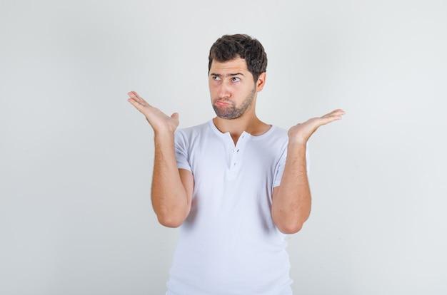 Jovem de camiseta branca levantando as palmas das mãos para cima e olhando para longe e parecendo pensativo