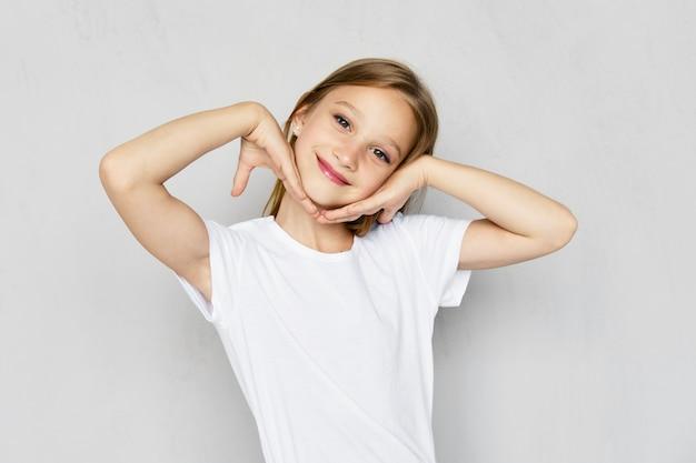 Jovem de camiseta branca segura a palma das mãos perto das bochechas