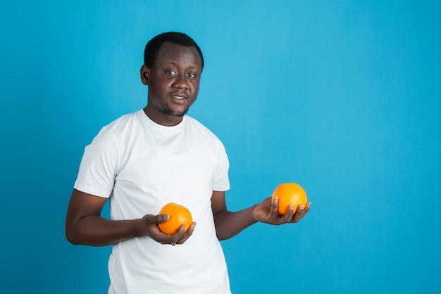 Jovem de camiseta branca segurando duas frutas de laranja doce contra uma parede azul