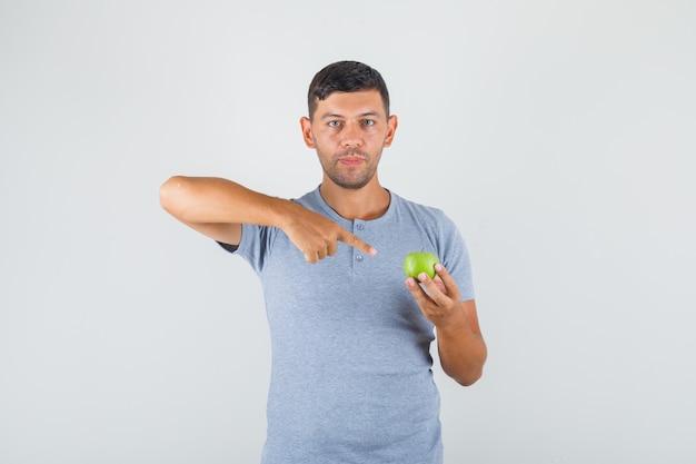 Jovem de camiseta cinza apontando o dedo para uma maçã verde