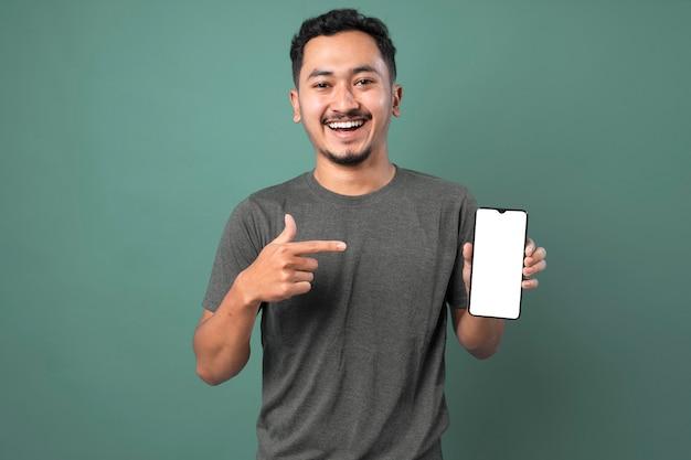 Jovem de camiseta cinza apresentando smartphone e apontando com o dedo para uma tela em branco