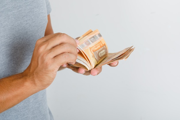 Jovem de camiseta cinza contando notas de euro