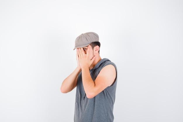 Jovem de camiseta cinza e boné cobrindo o rosto com as mãos, olhando por entre os dedos e parecendo irritado