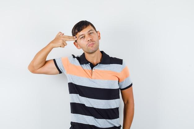Jovem de camiseta fazendo gesto de suicídio e parecendo sério