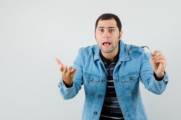 Jovem de camiseta, jaqueta segurando óculos, fazendo gesto de pergunta