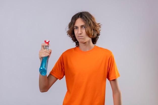 Jovem de camiseta laranja segurando spray de limpeza, olhando para a câmera com uma expressão triste no rosto, de pé sobre um fundo branco