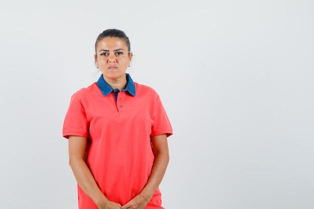 Jovem de camiseta vermelha em pé em linha reta e posando e olhando sério, vista frontal.