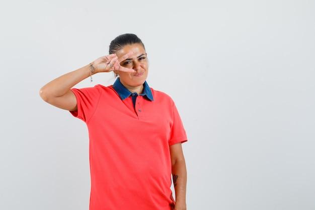 Jovem de camiseta vermelha, mostrando o sinal de v no olho e parecendo feliz, vista frontal.