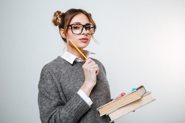 Jovem de camisola e óculos segurando livros