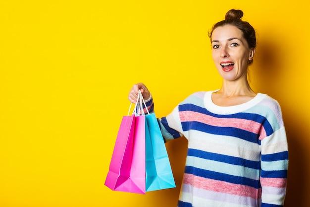 Jovem de camisola segurando sacolas de compras em fundo amarelo.