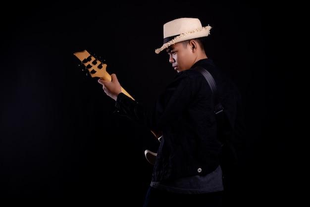 Jovem de casaco de couro preto com guitarra elétrica