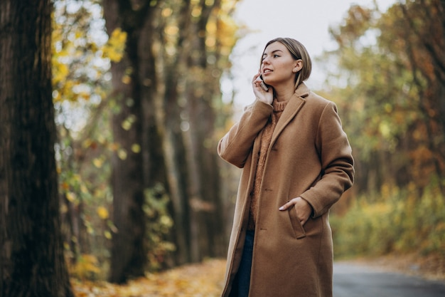 Jovem de casaco em pé na estrada em um parque de outono