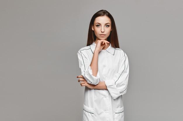 Jovem de casaco médico branco posando para o fundo cinza, copie o espaço para sua publicidade. conceito de saúde. modelo feminino na imagem de um médico