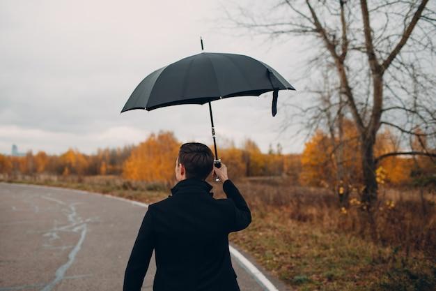 Jovem de casaco preto andando na chuva com guarda-chuva