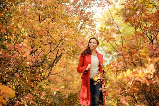 Jovem de casaco vermelho andando no parque ensolarado de outono com folhas amarelas