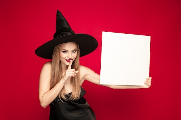 Jovem de chapéu como uma bruxa em fundo vermelho