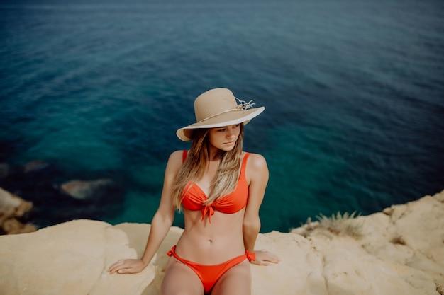 Jovem de chapéu de palha e biquíni sentada na ponta de uma rocha com o mar