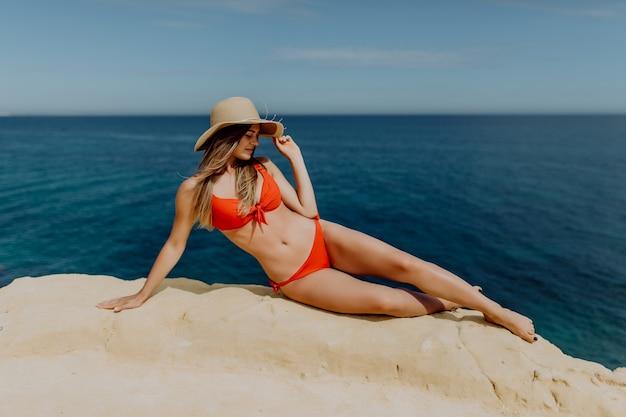 Jovem de chapéu de palha e biquíni vermelho deitado na borda da pedra com bela vista sobre o oceano.