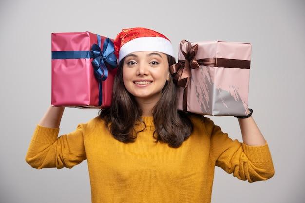 Jovem de chapéu de papai noel segurando em caixas de presente de mãos.