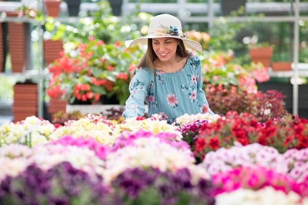Jovem de chapéu de sol comprando plantas em um berçário