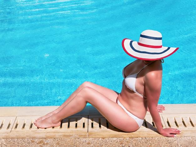 Jovem de chapéu de sol, tomando banho de sol à beira da piscina, vista superior.