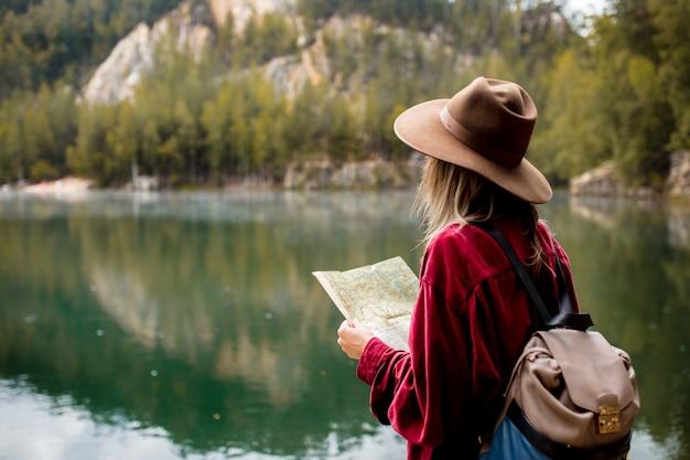 Jovem de chapéu e camisa vermelha com mapa perto do lago