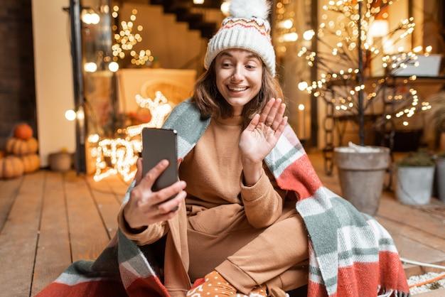 Jovem de chapéu e xadrez comemorando sozinha as férias de ano novo no terraço em casa, tendo uma videochamada no telefone. conceito de quarentena e auto-isolamento durante a epidemia nos feriados