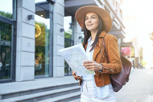 Jovem de chapéu usando mapa enquanto caminha ao ar livre