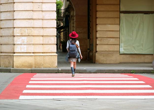 Jovem de chapéu vermelho andando na faixa de pedestres vermelha e branca