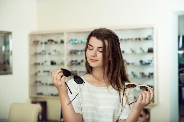 Jovem de compras, segurando dois pares de óculos de sol elegantes