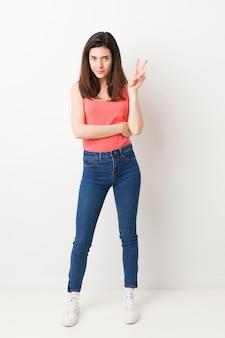 Jovem de corpo inteiro em branco mostrando o número dois com os dedos.