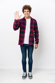 Jovem de corpo inteiro sorrindo alegre mostrando número cinco com os dedos