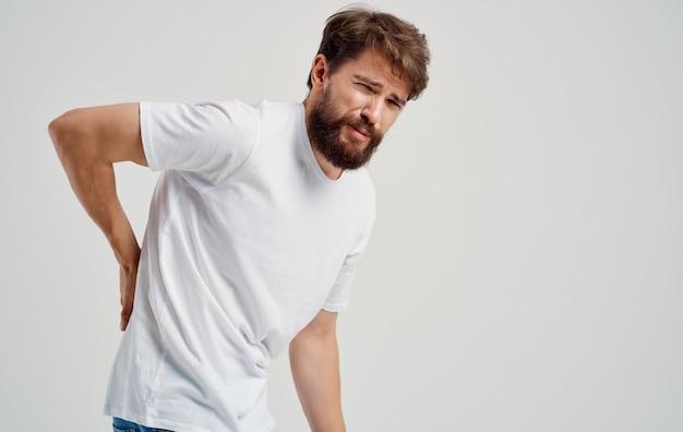 Jovem de dor nas costas em morena de bigode de barba de camiseta. foto de alta qualidade