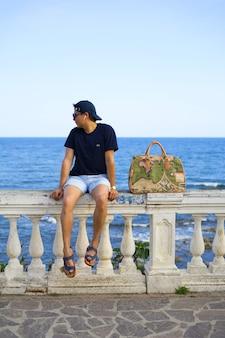 Jovem de férias esperando sentado e olhando o horizonte e com uma mala de viagem
