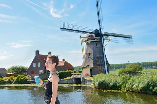 Jovem de férias na holanda, olhando o moinho de vento holandês de uma barcaça em um cruzeiro pelo canal