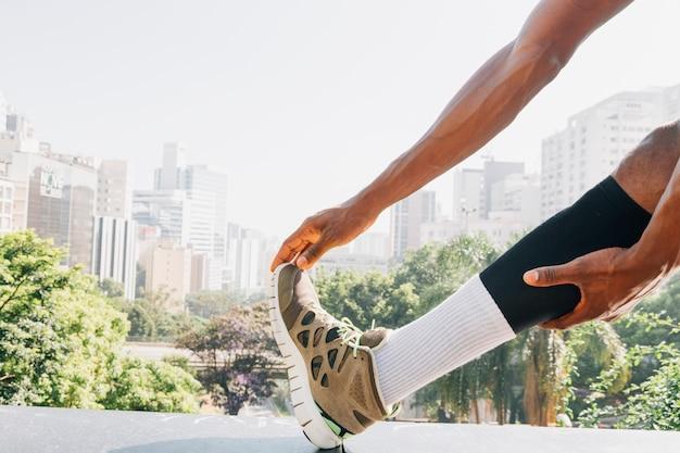 Jovem de fitness, esticando os músculos da perna contra o horizonte da cidade