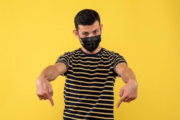 Jovem, de frente, com camiseta listrada em preto e branco, apontando para o chão com fundo amarelo