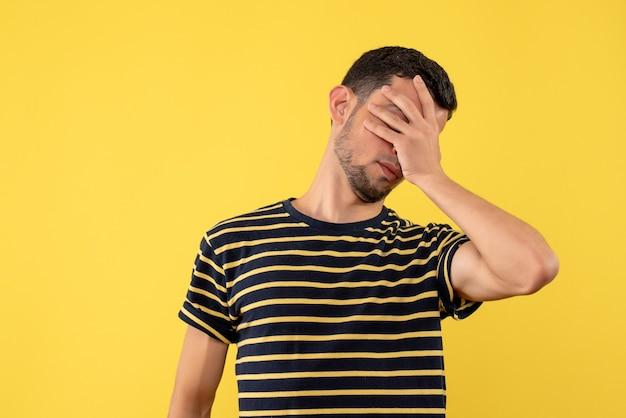 Jovem, de frente, com camiseta listrada em preto e branco, cobrindo os olhos com a mão amarela isolada no fundo