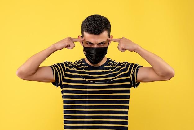 Jovem, de frente, com camiseta listrada em preto e branco, colocando os dedos na têmpora em fundo amarelo