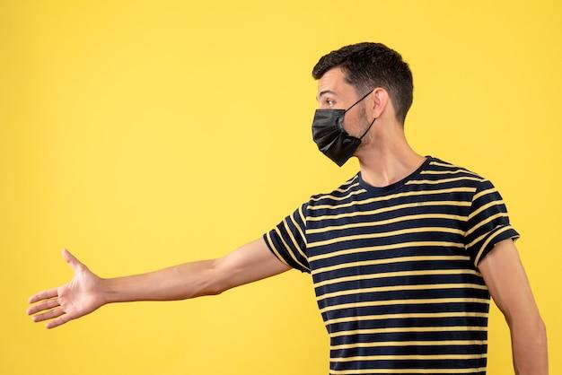 Jovem, de frente, com camiseta listrada em preto e branco, dando a mão sobre fundo amarelo