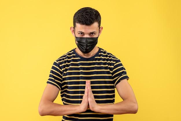 Jovem, de frente, com camiseta listrada em preto e branco, dê as mãos em um fundo amarelo