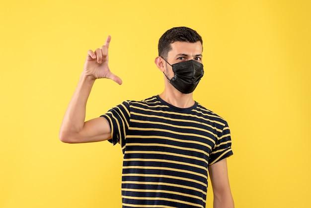 Jovem, de frente, com camiseta listrada em preto e branco, em pé sobre fundo amarelo