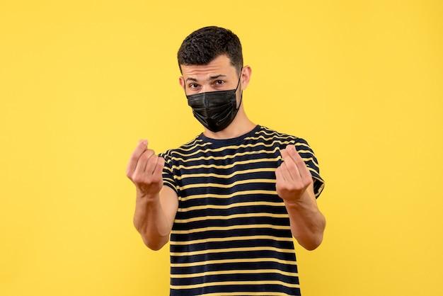Jovem, de frente, com camiseta listrada em preto e branco fazendo sinal de dinheiro com o dedo em fundo amarelo isolado