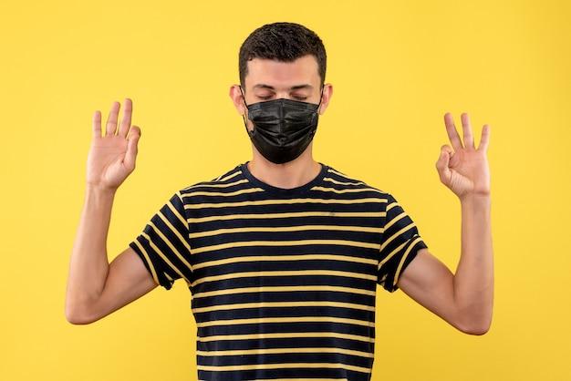 Jovem, de frente, com camiseta listrada em preto e branco, fechando os olhos no fundo amarelo