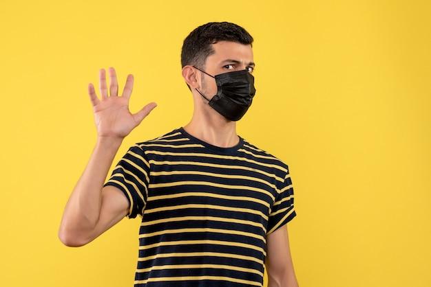 Jovem, de frente, com camiseta listrada em preto e branco, levantando a mão sobre fundo amarelo