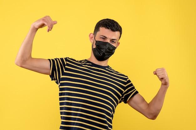 Jovem, de frente, com camiseta listrada em preto e branco, mostrando força em fundo amarelo
