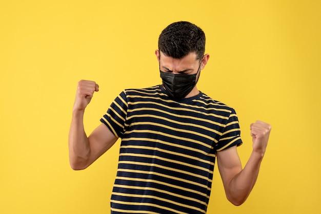 Jovem, de frente, com camiseta listrada em preto e branco, mostrando o gesto vencedor em fundo amarelo