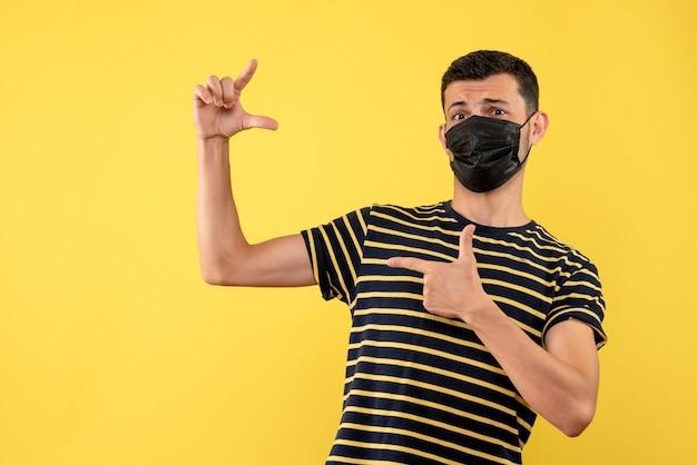 Jovem, de frente, com camiseta listrada em preto e branco mostrando o tamanho com a mão sobre fundo amarelo